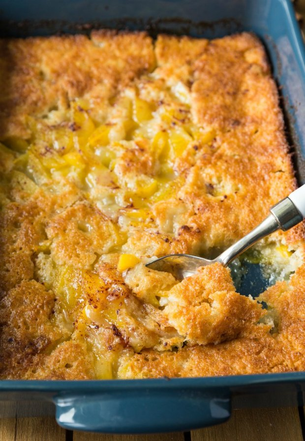 Spoon in peach cobbler in baking dish
