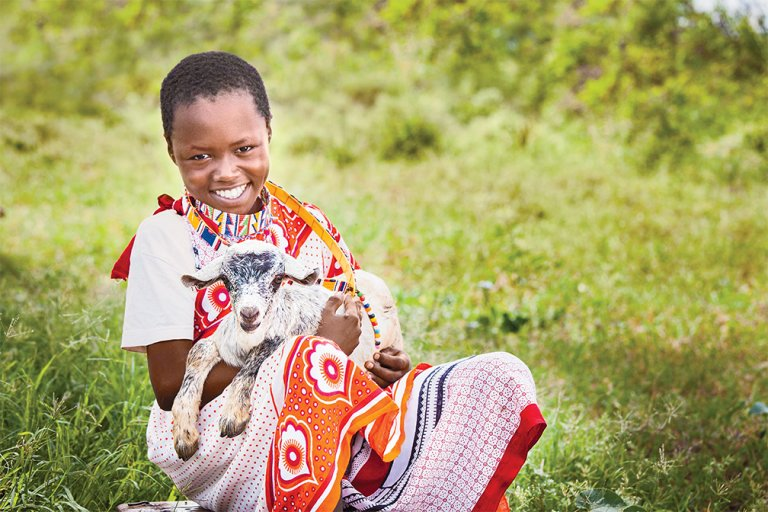 Benson, age 8, with a goat in Mashuru ADP.