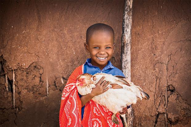 Mlonra, age 7, with a chicken in Mashuru ADP.