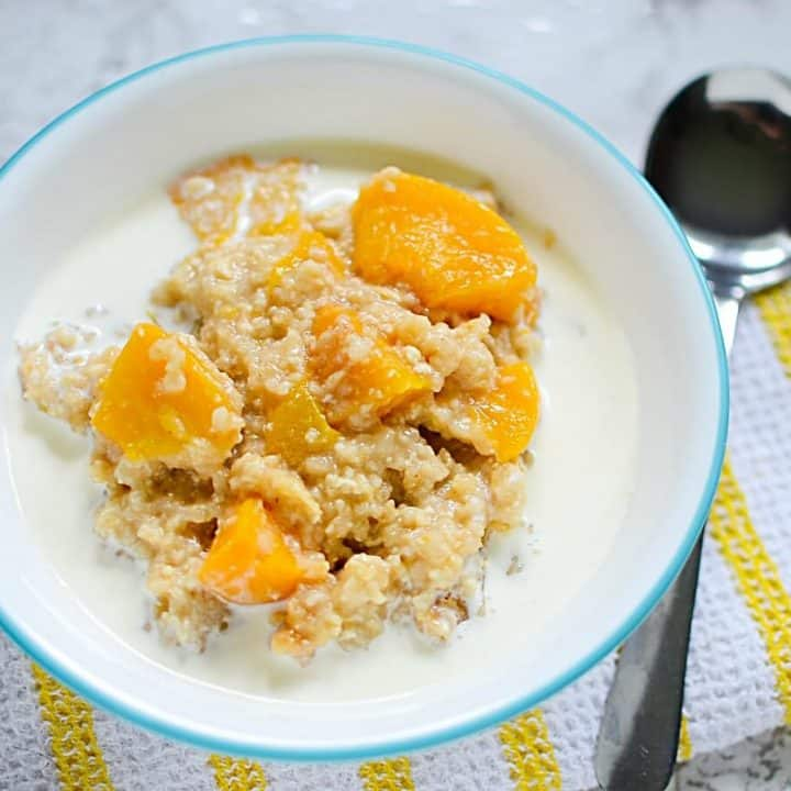 Ginger Peach Steel Cut Oats made in the slow cooker in a white bowl on a yellow and white towel