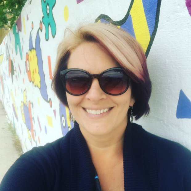 Fit In - Woman in front of street art in sunglasses
