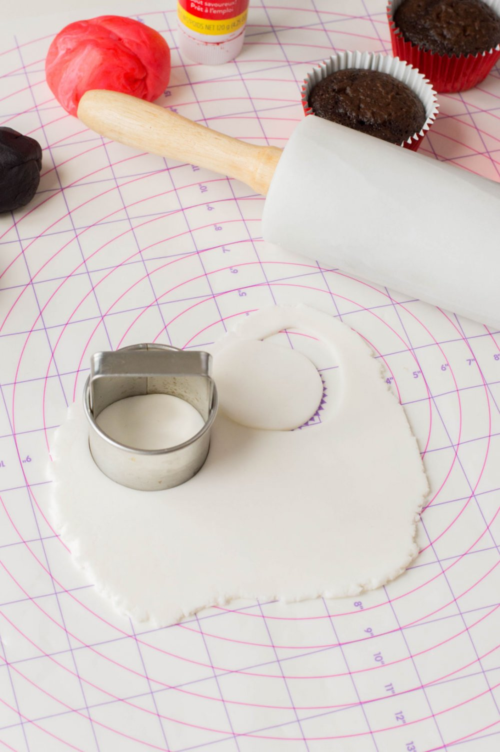 Using a cookie cutter to cut out white fondant