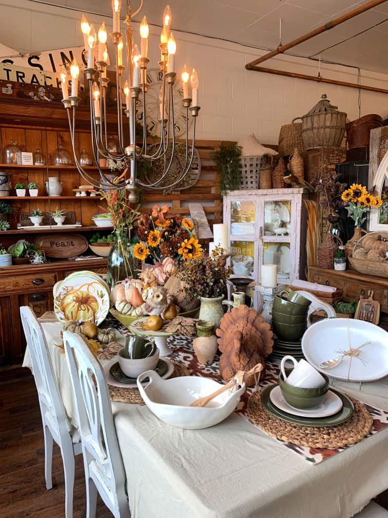 Fall vignette with green and white dishes, flowers and gourds.