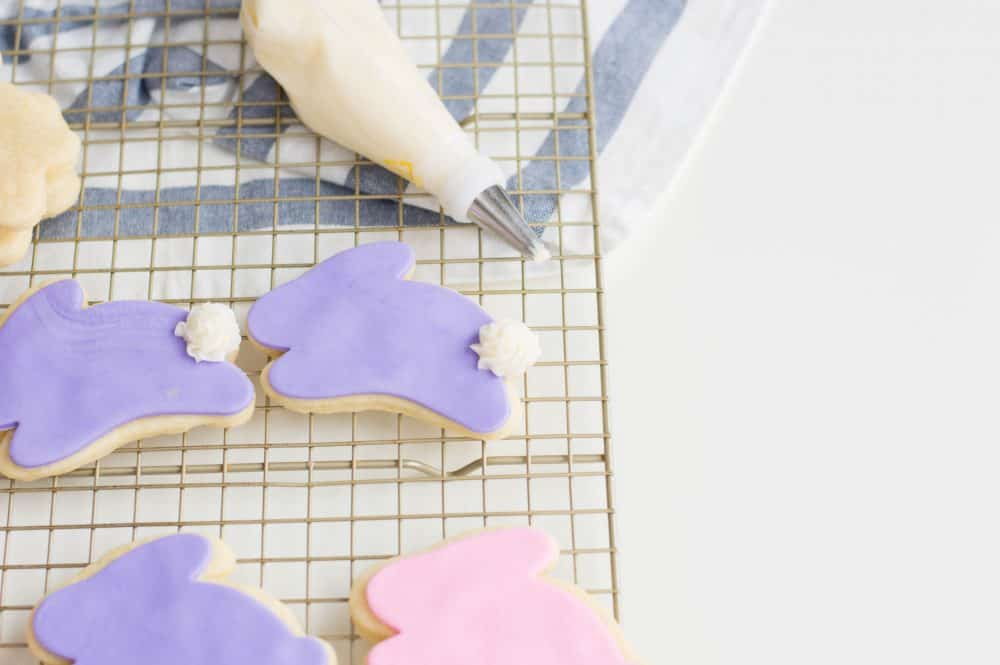 Adding tails to easter sugar cookies that are bunny shaped.