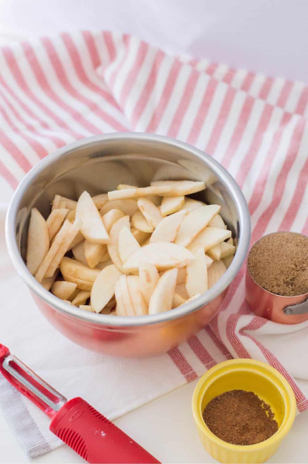 tossing apples with sugar, cinnamon, nutmeg for apple cobbler filling