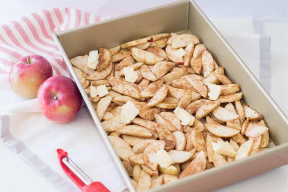 placing apple mixture in baking pan for snickerdoodle apple cobbler