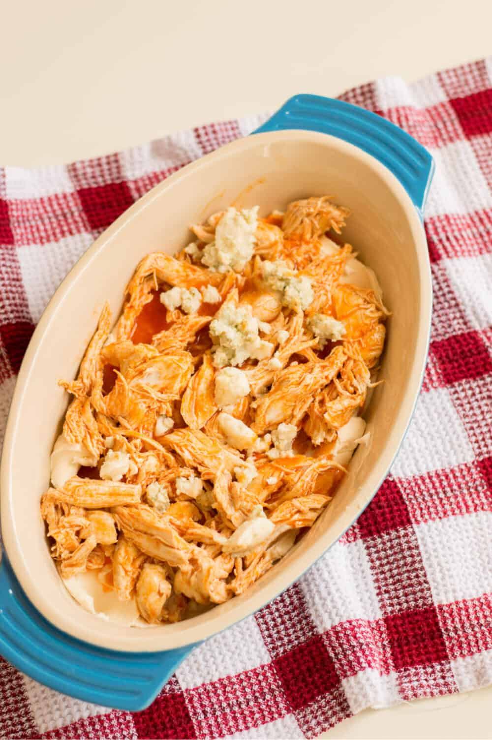 Layering chicken, cream cheese, and other ingredients for buffalo chicken dip appetizer
