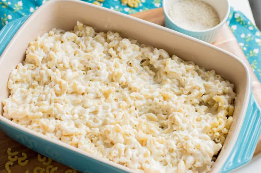 placing cooked macaroni mixed with cheese sauce in casserole dish
