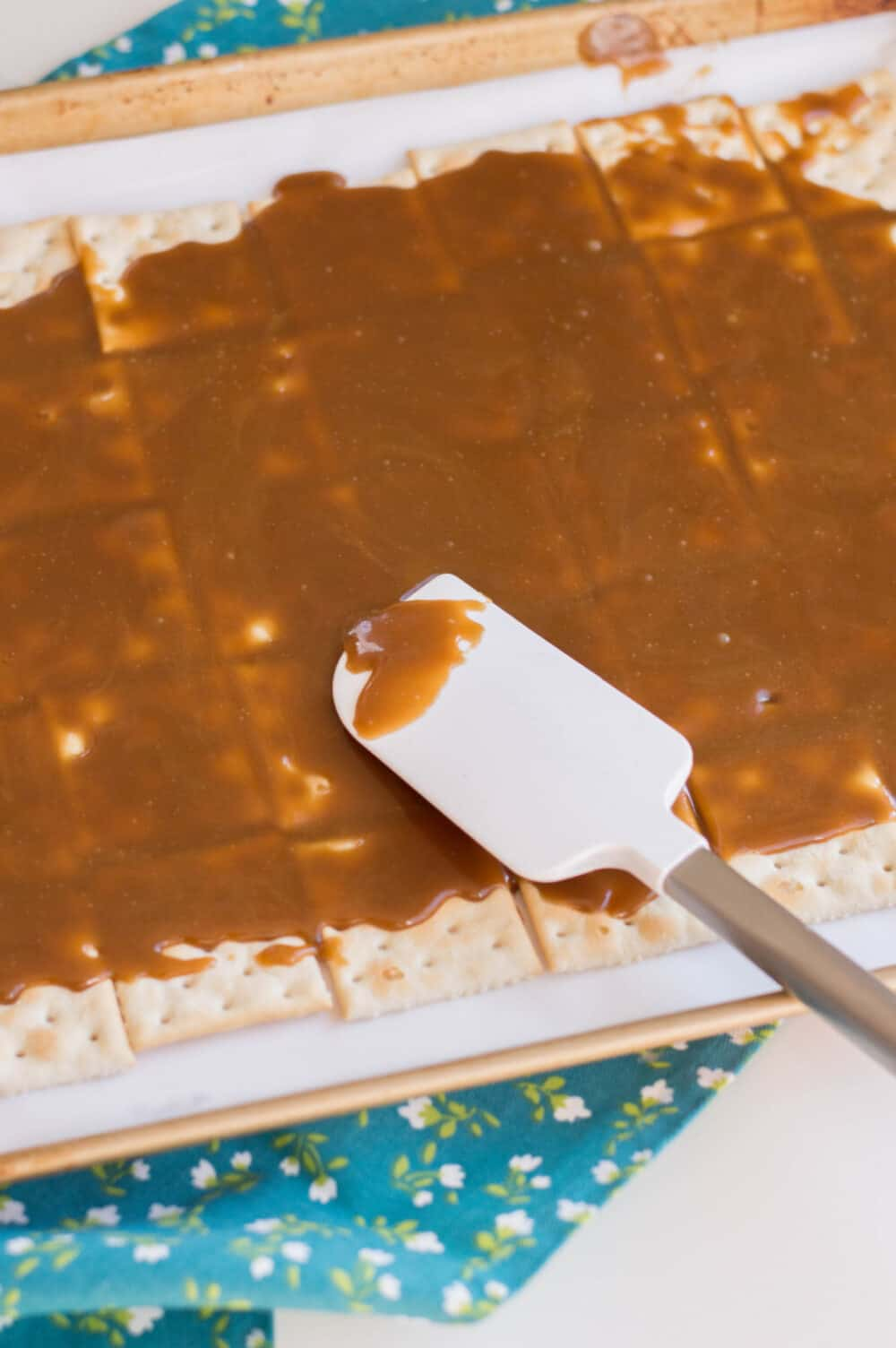 spreading melted butter and brown sugar mixture over crackers for christmas toffee