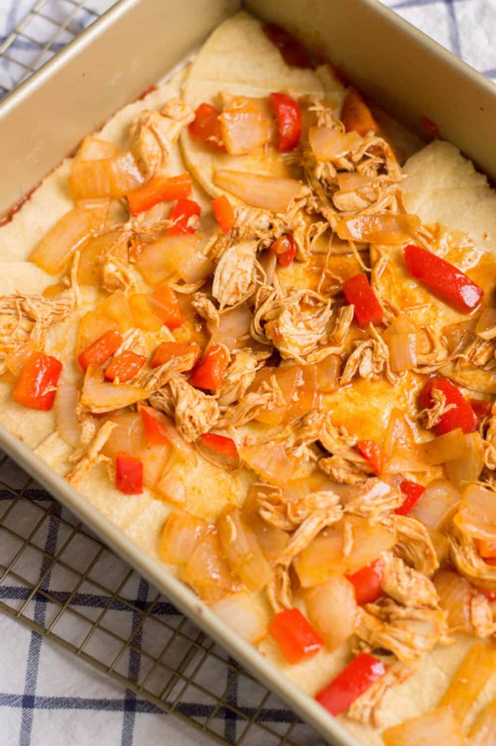 adding chicken mixture to chicken enchilada casserole