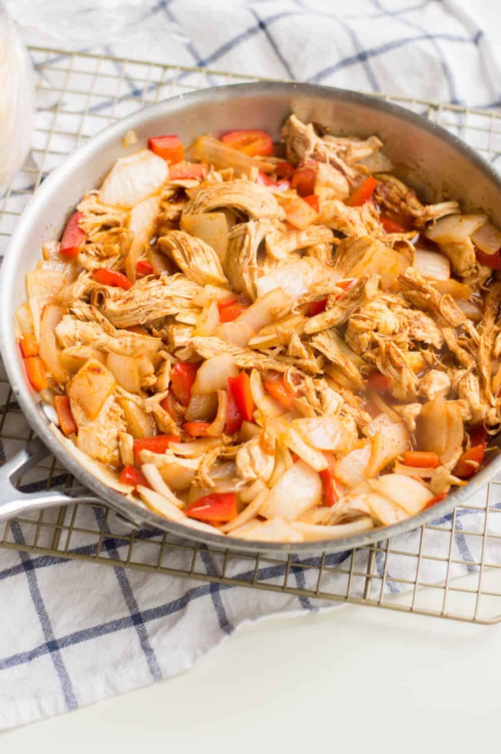 adding taco seasoning to chicken mixture for chicken enchilada casserole