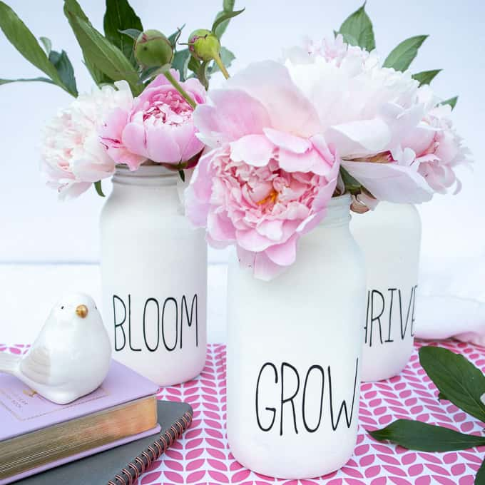 Chalk Painted mason jars with peonies on pink patterned tablecloth
